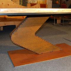 Geknickte Cortenstahl-Säul des Nußbaum-Tischs auf rechteckiger Bodenplatte aus dem gleichen Material