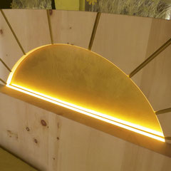 """Detail Zirbenholzbett """"Morgensonne"""": eingefräste, golden lackierte Sonne im Kopfteil mit LED-Beleuchtung am geraden unteren Rand"""