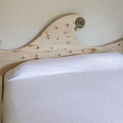 """Zirbenbett """"Waldfee""""  mit organisch geformtem Kopf- und Fußteil und Intarsie """"baskisches Lauburu"""""""