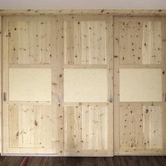 3-türiger Schwebetürenschrank aus Zirbe, auf allen Türen mittig eine Bauchbinde aus heller Schafwolle