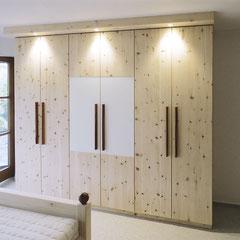 Schrank aus Zirbenholz mit weißer Glasauflage auf zwei Türen und Griffleisten aus Nussbaum
