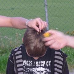 Ballonfahrertradition: Ein paar Haare werden abgesengt und schnell mit Bier gelöscht. Alexander hat Spaß dabei.