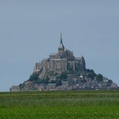 Von weit her sieht man den Mont St. Michel aus dem Meer aufragen.