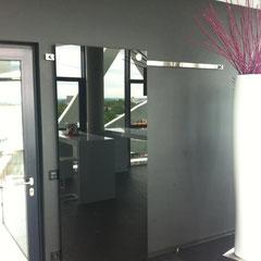 Schiebtür aus schwarz lackiertem Glas als Schreibtafel