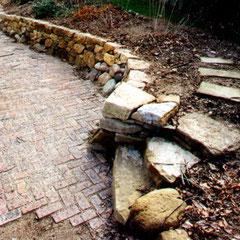 Dry stone retaining wall, private garden, Kent, OH utilizing a mixture of native granite and sandstone.