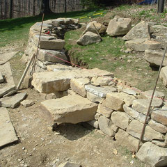Dry stone retaining wall under construction; stile stones quarried and cut of native sandstone, private client, Kent, Ohio.
