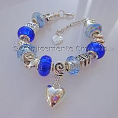 BR.AC_038  Bracciale Pandora Style in acciaio nei toni celeste ed azzurro. Charm a forma di cuoricino. Chiusura con moschettone e catenella di allungamento.