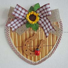 n. 27 Targhetta portafortuna a forma di cuore su sottopentola flessibile in materiale tipo bambù a costine rilegate.  Bordo cuore in tessuto.  (cm 14 x 14 x 0,4) con decorazioni varie