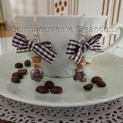 n. 18 orecchini a pendente bottiglietta in vetro con all'interno piccolissimi chicchi di caffè in fimo. Fiocchetto a quadretti bianco/marrone. Senza nickel.