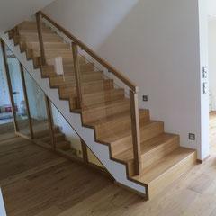 Treppenaufgang ins Obergeschoss. Betontreppe mit Eichenstufen belegt und passendem Treppengeländer aus Holzpfosten mit Glasscheiben.