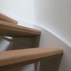 Treppe mit deckend lackierten Wangen und eingestemmten Holzstufen aus Eiche.