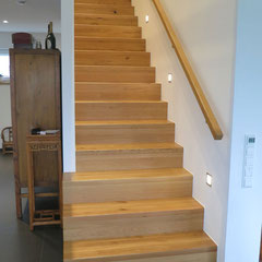 Betontreppe mit Tritt- und Setzstufen belegt. Die Stufen sind aus Eiche mit durchgehenden Lamellen.