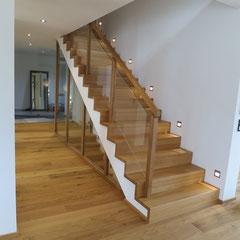 Das Treppengeländer ist aus Eichenholz mit Scheiben aus Klarglas.