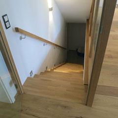 Betontreppe mit Eichenstufen belegt und Wandhandlauf ebenfalls aus Eiche ergänzt.