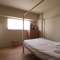 寝室にはウッドフレーム付きのベッド