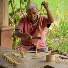 Laos, Luang Prabang: splitting bamboo to make toy birds at The Living Land, a community farm project
