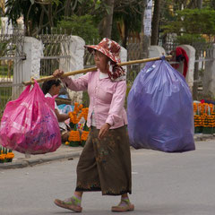 Laos, Luang Prabang: a vendor carrying goods on Kitsalat Street
