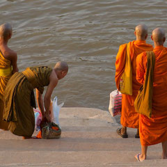 Laos, Luang Prabang: monks beside the Mekong awaiting the arrival of a water taxi