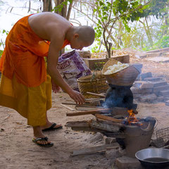 Laos, Luang Prabang: a novice monk preparing to heat up sticky rice at Wat Khok Pab