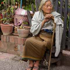 Laos, Luang Prabang: an elderly woman at the morning market by the National Museum