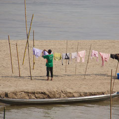 Laos, Luang Prabang: hanging laundry to dry on a sandbank in the Mekong river