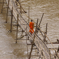Laos, Luang Prabang: a novice monk crossing the temporary bridge across the Nam Khan river