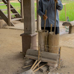 Laos, Luang Prabang: Blacksmith using bellows to heat his forge at The Living Land