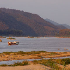 Laos, Luang Prabang: boats travelling up the Mekong River at sunset