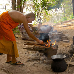 Laos, Luang Prabang: a novice monk preparing to re-heat sticky rice at Wat Khok Pab