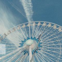 Riesenrad in Marseille mit blauem Himmel und Schleierwolken.