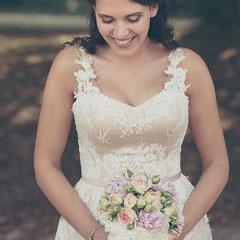 Die Braut blickt zu ihrem Brautstrauß - aufgenommen im Staatspark Hanau Wilhelmsbad.