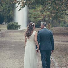 Das Brautpaar läuft Hand in Hand einen Weg im Schloss Philippsruhe entlang. Im Hintergrund ist die Wasserfontäne zu sehen.