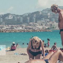 Strandszene am Stadtstrand von Marseille mit zwei älteren Menschen. Im Hintergrund ist die Stadt zu sehen.