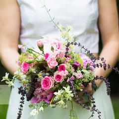 Als Hochzeitsfotograf Hanau auf der Hochzeitsfeier im Kinzigheimer Hof Bruchköbel. Die Braut hält den bunten Brautstrauß vor sich.