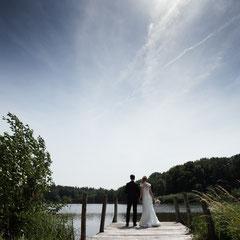 Ein Brautpaar blickt auf den Weiher während des Brautpaar Fotoshootings am Weiherhof in Wächtersbach.