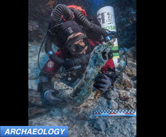 Diver recovering ancient statue Greek shipwreck