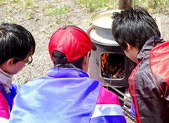 ジュニア冒険キャンプ「わくわく東いぶり隊」イメージ写真 七輪で魚を焼く子ども
