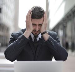 Mann im Anzug sitzt vor seinem Computer und fässt sich verzweifelt an den Kopf
