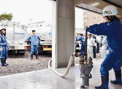 平岸配水池の敷地内にある緊急用施設のバルブを使い、タンク車に水を送る職員ら(6月23日北海道新聞朝刊21面より)