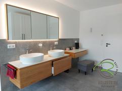 Waschtischunterschrank in Eiche massiv von Schreinerei Holzdesign Ralf Rapp in Geisingen mit Spiegelschrank und Schminktisch mit weißer Aufsatzplatte