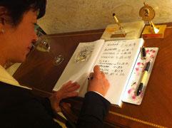 大使館入館時に芳名録に記載しているところ。
