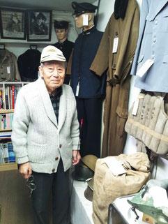 館長の川野喜一さんと、展示されている相良六男中尉のライフジャケット(右)