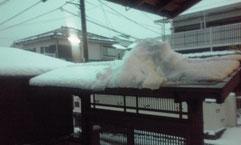 門の屋根の上に、その上からの雪が落ちて。