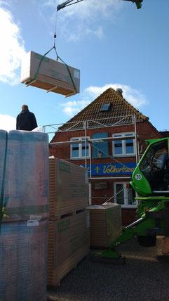 Mit dem Kran wird das material fürs Dach abgeladen