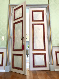 Leicht geöffnete Tür in Marmor Optik. Durch den Spalt ist die Eingangshalle des Herrenhauses zu sehen.