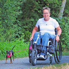 Monika Wagner. Eine Frau im Rollstuhl mit einem kleinen Hund