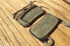 Genutzte Bremsbeläge, die bald ersetzt werden sollten, da sonst die Bremsscheibe demnächst durch Spreizfeder und später die Trägerplatte beschädigt wird.