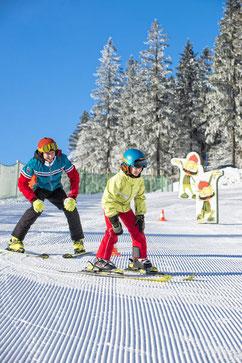 Erwachsener und Kind auf einer Spiel-Skipieste - Skikurs
