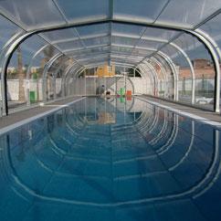 Cobertor alto telescópico de piscina en el suelo, motorizado con las motorizaciones de ruedas AKIA