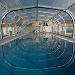 High, flat telescopic swimming pool enclosure motorised with AKIA wheeled motor drives